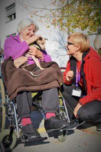 Obisk v Domu starejših Laško, Senna sedi starejši uporabnici v naročju, gospa jo ljubkuje in se pogovarja s Heleno.